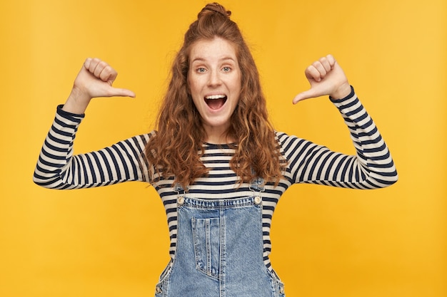 Indoor shot of young ginger female wears stripped shirt and denim overalls pointing with both thumbs at her self, feels happy and strong. isolated over yellow wall