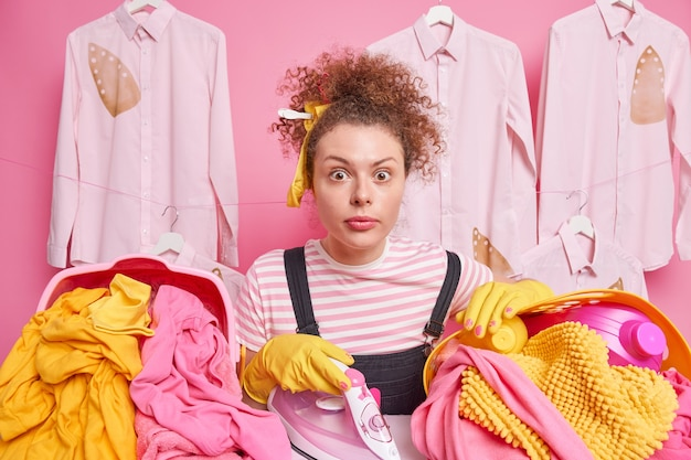 Indoor shot of young girl with curly hair surrounded by basket of laundry irons washed line has surprised gaze  poses at ironing board poses against pink wall busy stroking things