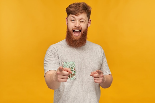 Indoor shot of young handsome ginger male with a big beard, pointing with both hands at front, smiles and wink