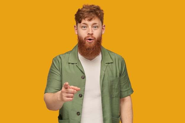 Indoor shot of young handsome redhead man with big beard, looking directly at front with shocked, astonished facial expression, pointing with finger