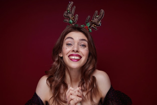 Indoor shot of young joyful lovely brunette with wavy hairstyle enjoying x-mas theme party masquerade and smiling happily, dressed in elegant clothes