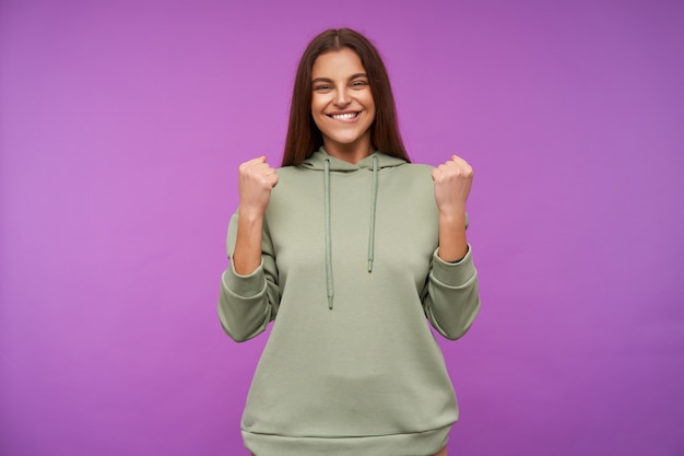 Indoor shot of young joyful pretty brunette lady raising happily her fists while rejoicing about something, smiling widely while standing over purple wall