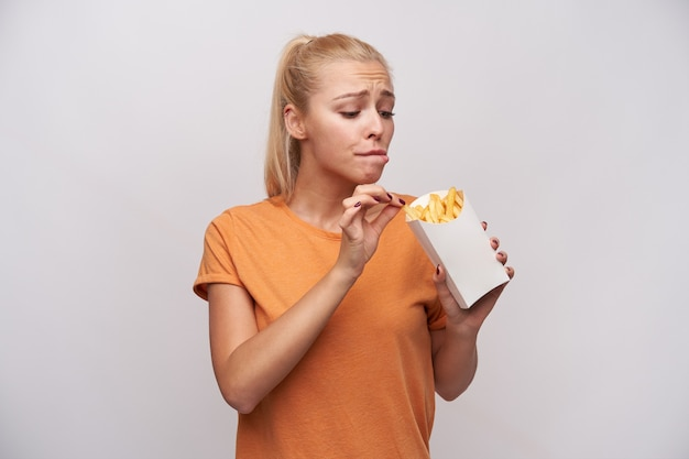 Indoor shot of young long haired blonde lady keeping paper box with french fries and looking excitedly at it, wanting to eat it, but worrying about extra calories, isolated over white background