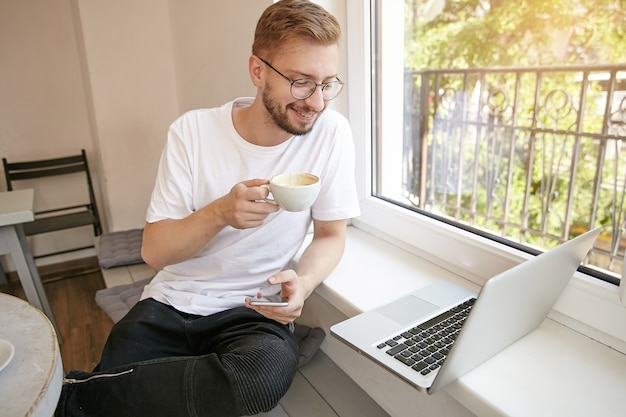 Indoor shot of young lovely bearded guy, sitting next to window with phone in his hand and laptop on windowsill, drinking coffee and looking to screen with smile