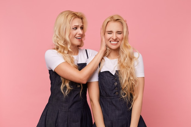 Indoor shot of young lovely white-headed cheerful woman covering ears of her glad blonde sister with raised palms while posing over pink background together