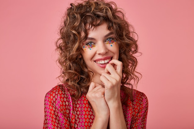 Indoor shot of young lovely woman with curls, smiling widely and touching her face, looking pleased and happy, isolated