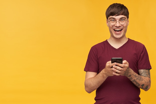 Indoor shot of young male student, smiles broadly while reading good news, wears red t-shirt and hold his phone in hands