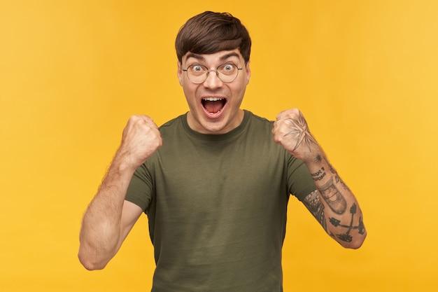 Colpo al coperto di un giovane maschio, indossa una maglietta verde e occhiali rotondi alla moda, urlando con la bocca e gli occhi ampiamente aperti mentre guarda la partita di calcio