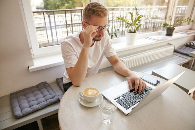 Tiro al coperto di giovane uomo pensieroso in maglietta bianca, seduto al tavolo con il computer portatile, bere caffè e toccare i suoi occhiali, lavorando in remoto al caffè della città