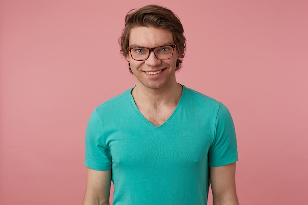 Indoor shot of young positive male, wears stylish glasses and blue t-shirt, looks directly into camera with broad smile, feels happy