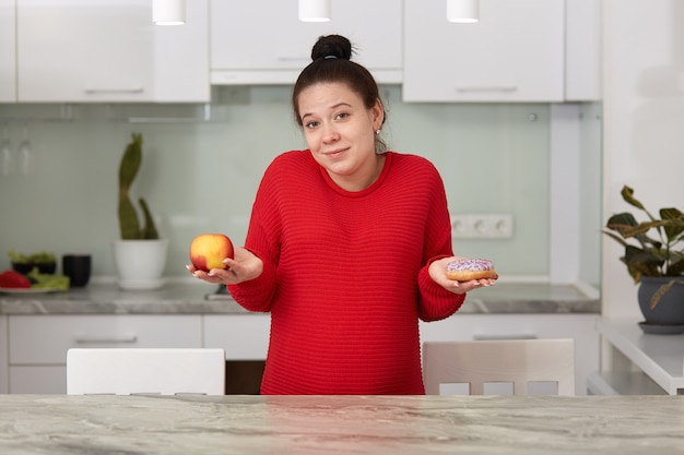 Indoor shot of young pregnant woman with apple and tasty cake in her hands, decides what to eat, attractive female posing in house kitchen.