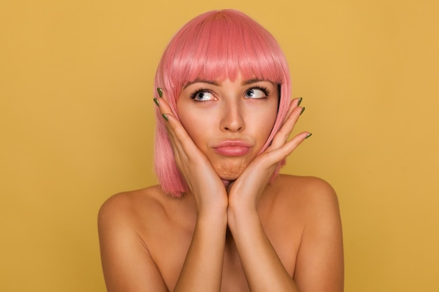 Indoor shot of young pretty blue-eyed lady with pink bob hairstyle holding her face with raised palms and looking upwards with puzzled face, posing over mustard wall