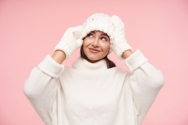 Indoor shot of young pretty brown haired woman touching her white hat with raised hands and smiling slightly, standing over pink wall in cosy clothes
