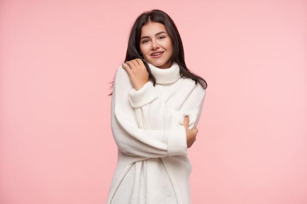 Tiro al coperto di giovane donna dai capelli abbastanza castani con trucco naturale che sorride leggermente mentre guarda positivamente davanti mentre si abbraccia, isolato sopra il muro rosa