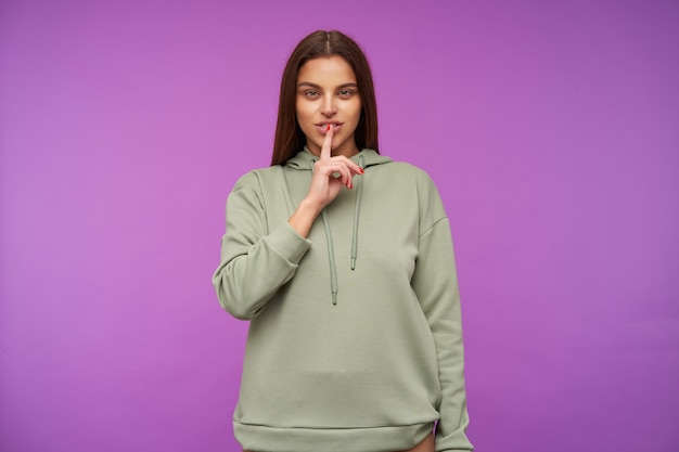 Indoor shot of young pretty brunette lady squinting her green eyes while holding forefinger on her lips, standing over purple wall in mint hoodie