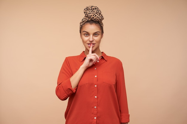 Indoor shot of young pretty brunette woman raising hand in hush gesture while asking to keep silence, isolated over beige wall in headband and red shirt