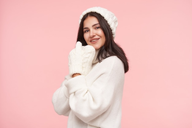 Indoor shot of young pretty brunette woman with natural makeup folding raised hands near her face and smiling positively to front, isolated over pink wall