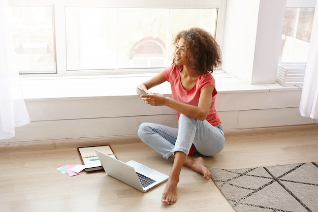 Indoor shot of young pretty curly woman sitting on floor with crossed legs, holding smartphone in hands and looking ahead with pleasant smile