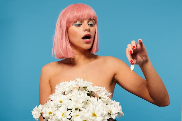 Indoor shot of young pretty naked pink haired woman with bob haircut posing in huge bouquet of flowers, looking at flower petal in raised hand