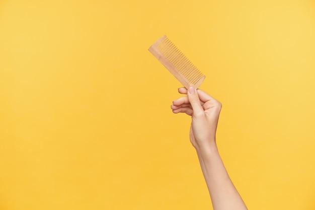 Tiro al coperto della mano della giovane donna graziosa che solleva la spazzola per capelli in legno mentre posa su sfondo arancione, giovane donna che esce e fa la pettinatura