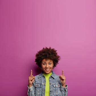 Tiro al coperto di giovane donna soddisfatta con i capelli ricci punta il dito indice verso l'alto, mostra lo spazio sul muro viola per la tua pubblicità, indossa abiti di jeans, sorride felice, promuove un posto al piano di sopra