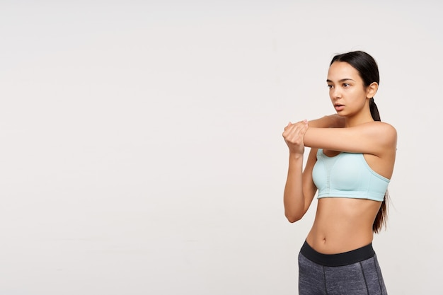Indoor shot of young slim brown haired woman dressed in mint top and grey leggins stretching her hands before workout while standing over white wall