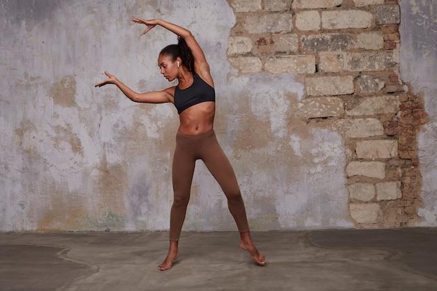 Tiro al coperto di giovane donna bruna dalla pelle scura sottile con acconciatura casual alzando le mani sotto la testa mentre impara a ballare sopra l'interno del soppalco, vestita con un comodo abbigliamento sportivo