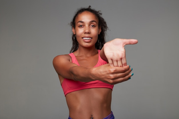 Indoor shot of young slim dark skinned female with curly long brown hair making stretching exercises while posing, looking with cheerful smile