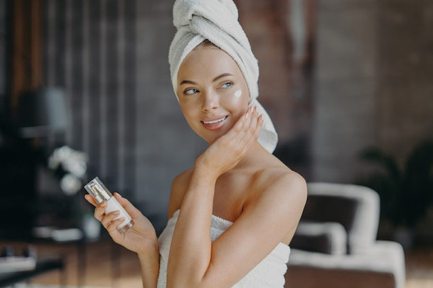 Indoor shot of young smiling woman applies moisturizer cream on face