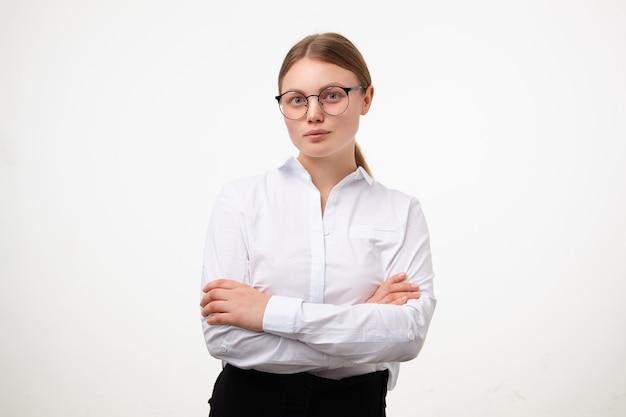 Tiro al coperto di giovane donna dalla testa bianca con gli occhiali tenendo le mani incrociate sul petto mentre guarda con calma la telecamera, in posa su sfondo bianco in abiti formali