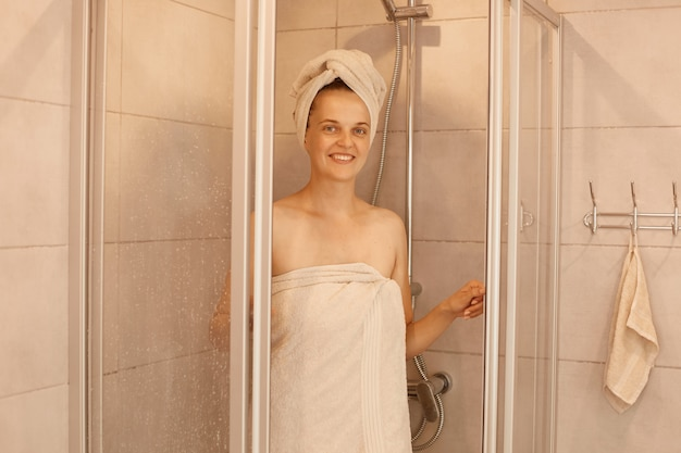 Indoor shot of young woman is getting out of the shower, standing wrapped in white towels, looking at camera with happy facial expression, morning routine.