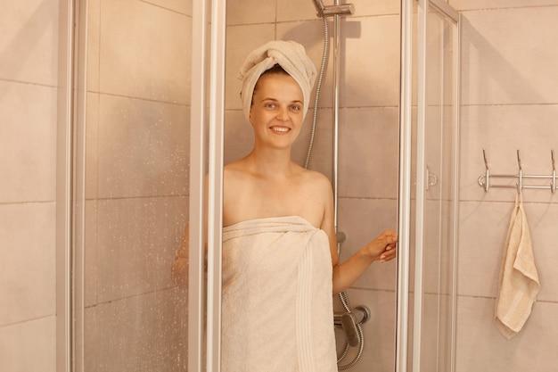 Il tiro al coperto di una giovane donna sta uscendo dalla doccia, in piedi avvolta in asciugamani bianchi, guardando la telecamera con un'espressione facciale felice, routine mattutina.