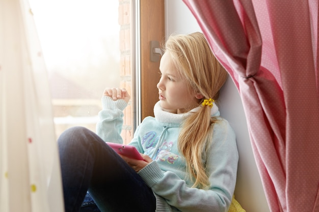 Indoor sideways portrait of beautiful female child with blonde hair relaxing at home on windowsill