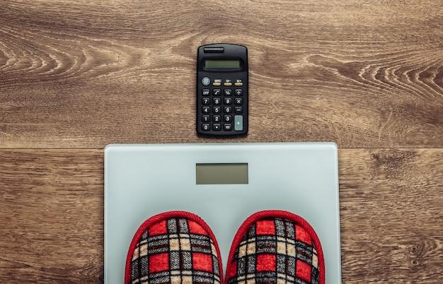 Домашние тапочки на напольных весах и калькуляторе.