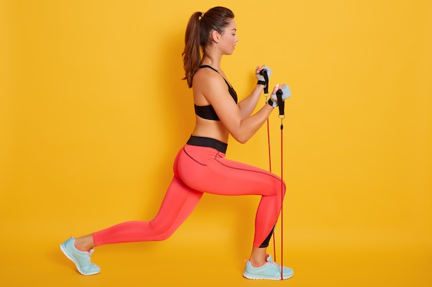 Indoor strong woman dressed black bra and leggins, using resistance band in her exercising at home, fitness model workout isolatedbon yellow. strength and motivation concept.