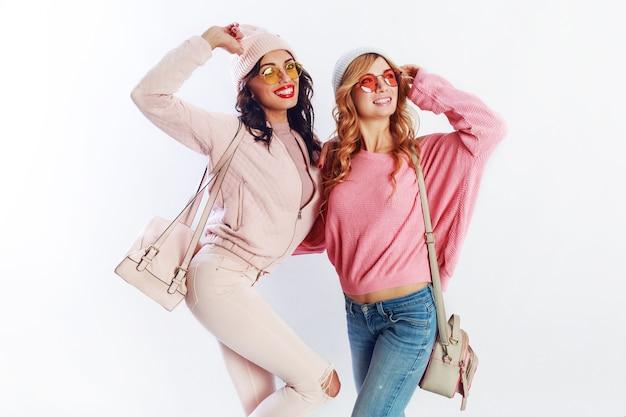 Immagine dello studio dell'interno di due ragazze, amici felici in vestiti rosa alla moda e ortografia del cappello divertente insieme. sfondo bianco. cappello e occhiali alla moda che mostrano pace.