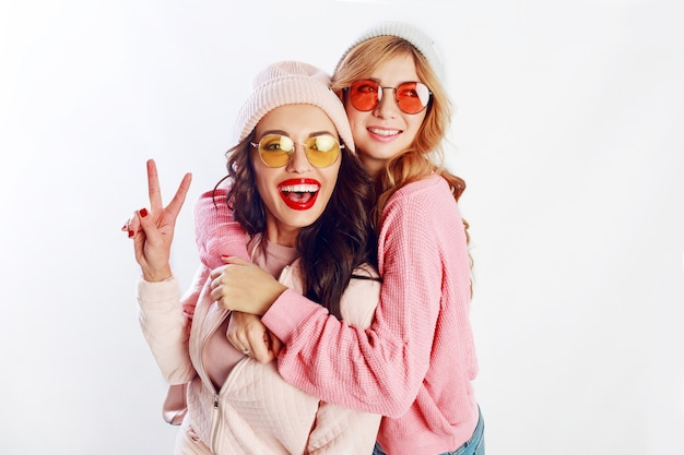 Indoor studio image of two girls, happy friends in stylish pink clothes and hat spelling funny  the together. white background