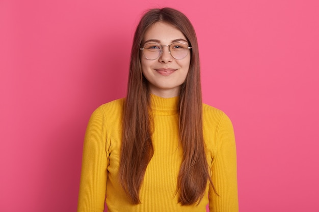 Indoor studio shot of attractive beautiful pretty young woman wearing eyeglasses and yellow sweatshirt, having long fair hair, posing isolated over pink wall. people and emotions concept.