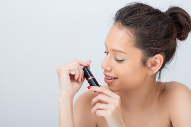 Indoor studio shot for beautiful asian woman smiling broadly applying lipstick