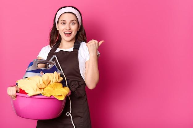 Indoor studio shot of cheerful emotional housewife posing isolated over pink