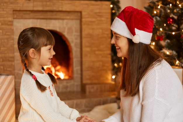 Indoor studio shot of dark haired woman wearing santa claus hat with her little daughter holding hands and looking at each other with great love. posing in festive living room near fireplace.