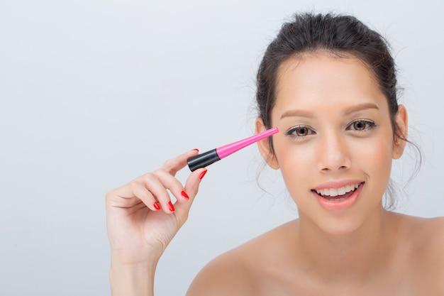 まつげに黒マスカラーを広く適用する笑顔の美しい白人女性の屋内スタジオ撮影