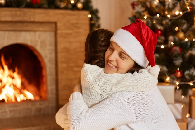 Indoor studio shot of mother and her little daughter hugging in festive room near fireplace and christmas tree, congratulating each other with new year eve.