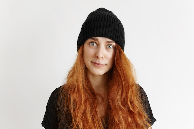 Крытый студийный снимок симпатичной рыжей хипстерской девушки в футболке и шляпе с возмущенным и обвиняющим взглядом