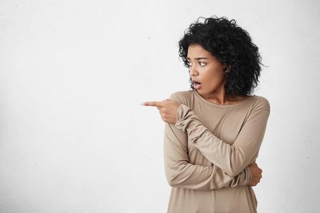Студийный снимок шокированной или удивленной брюнетки смешанной расы в повседневной одежде