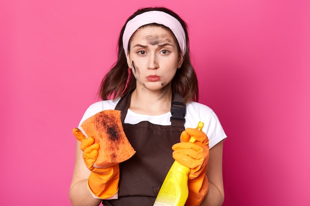 Indoor studio shot of upset disappointed housewife looking directly at camera, holding dirty washcloth and detergent, wearing cleaning gloves, headband and t shirt, brown apron. household concept.