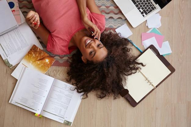 Вид сверху на красивую молодую кудрявую женщину с темной кожей, которая прерывает домашнее задание и звонит другу, лежа на ковре с книгами и заметками