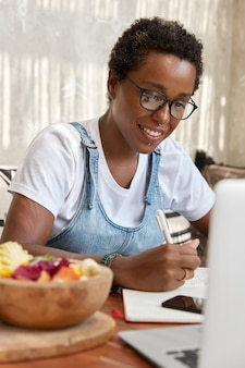 Colpo verticale dell'interno della ragazza afroamericana nera allegra guarda positivamente al monitor