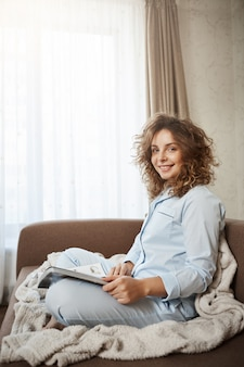 Indoor vertical shot of cute cozy wife with curly hair in nightwear sitting on sofa with blanket, reading magazine, enjoying perfect morning,