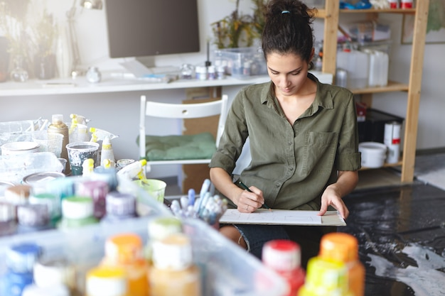 Indoor view of beautiful young caucasian woman artist with brunette hair busy making drawings in spacious workshop interior with lots of paint bottles